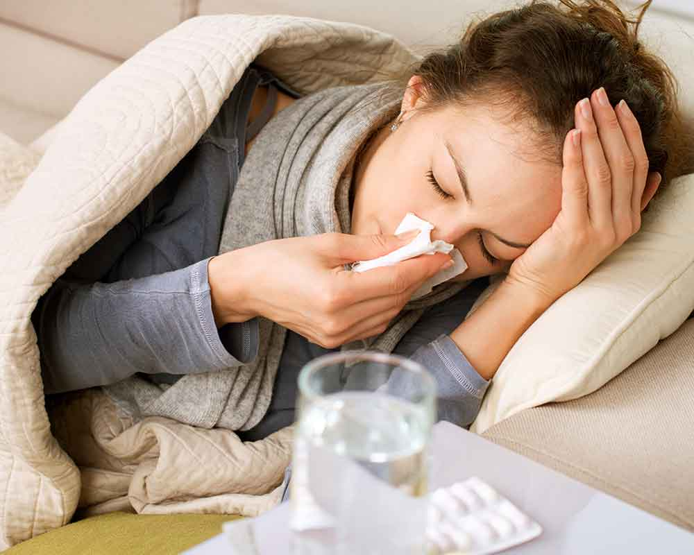 woman with colds wiping nose with white tissue