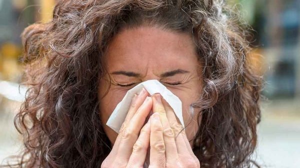 woman sneezing due to allergy