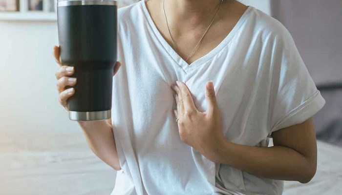 woman touching chest due to acid reflux