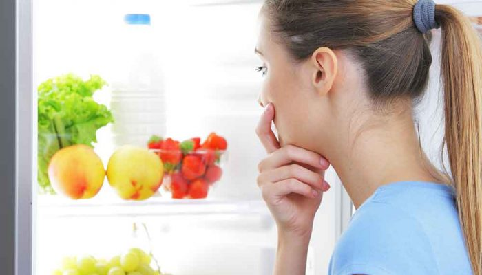 woman looking inside the fridge craving for something to eat