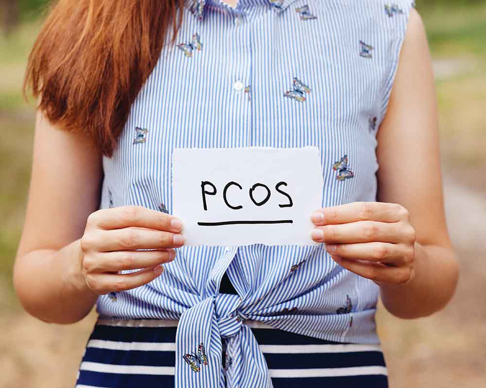 woman holding a white paper with PCOS text written