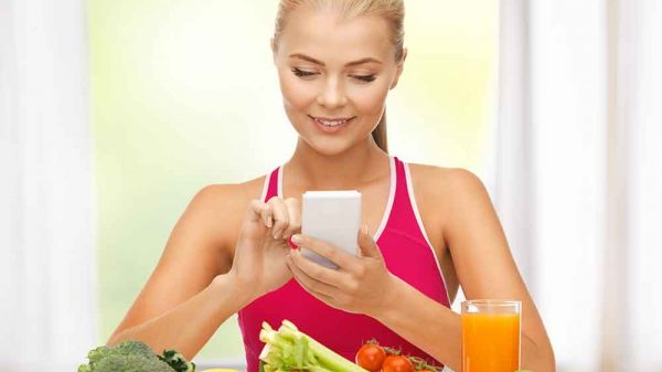 Fit woman sitting infront of fruits and veggies while counting macros using cellphone