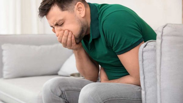 man sitting on the sofa covering mouth nauseous