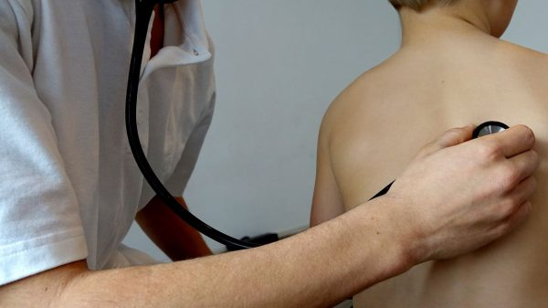 doctor checks patient's breathing using a stethoscope