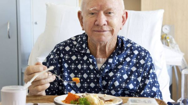 Old man eating on a hospital bed