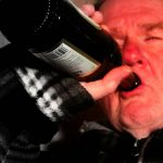 old man drinking a bottle of wine