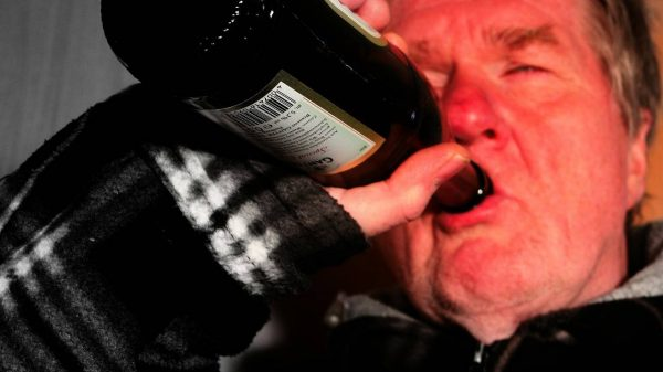 old man drinking a bottle of wine