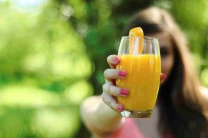 Young woman holding a glass of citrus juice