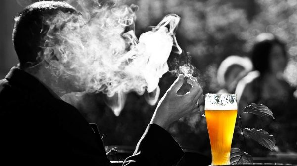 man covered with smoke from cigarette and a glass of beer