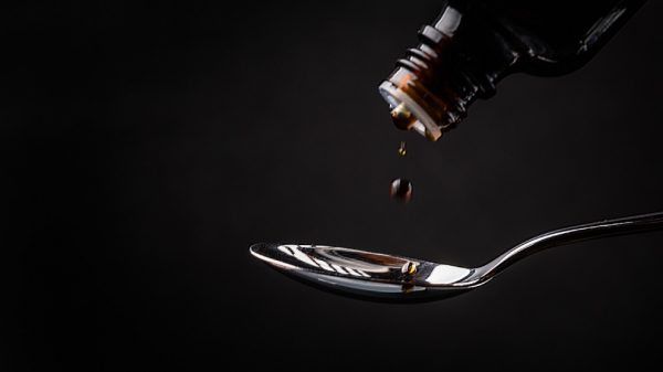Lactulose pouring on a silver spoon