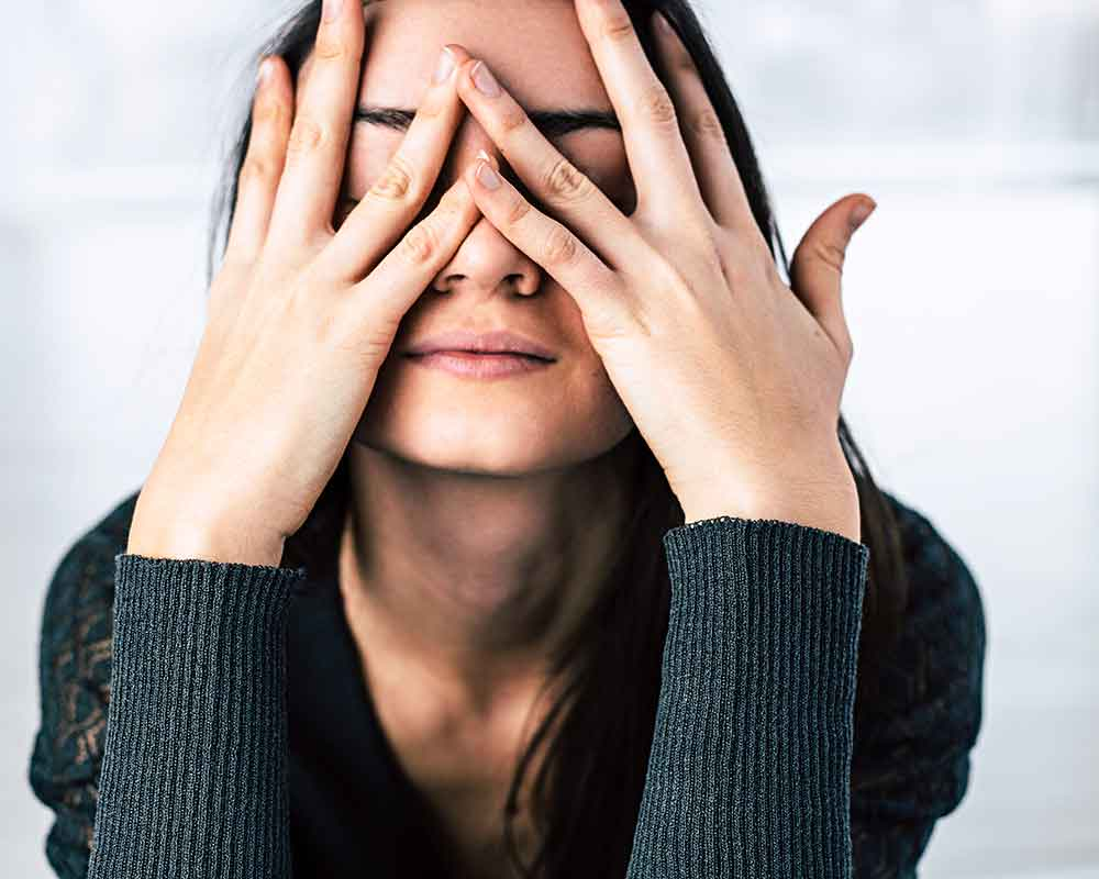 young woman covering face with fingers