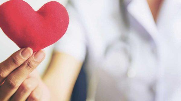 Nursing holding a small heart plush