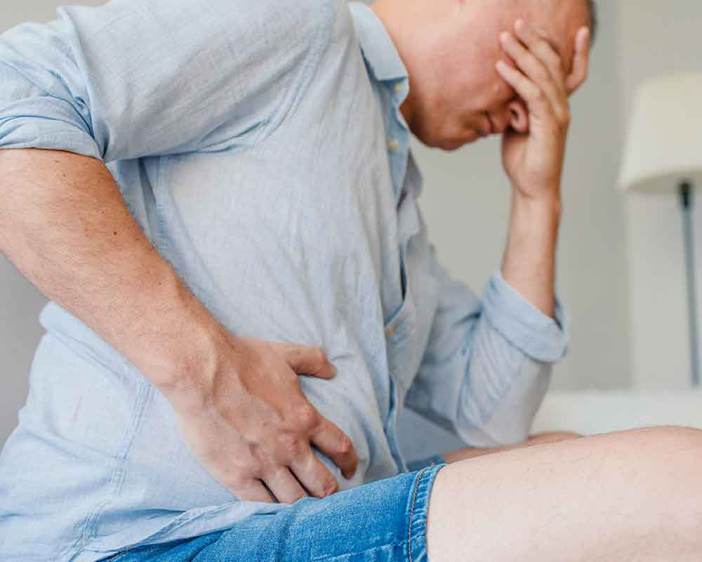 man holding face and tummy due to pain