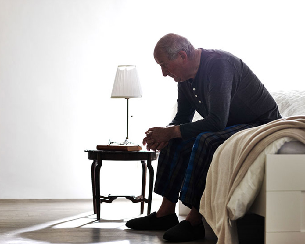 old man sitting on side of the bed