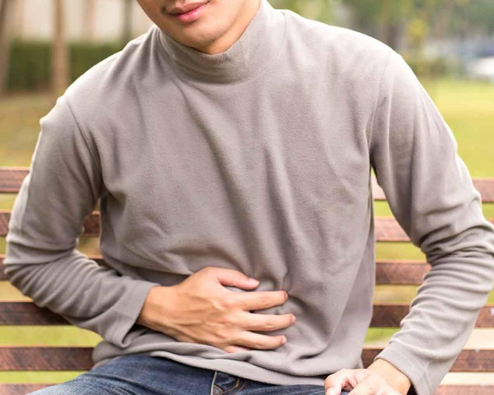 man sitting holding tummy