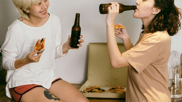 two ladies drinking beer and eating pizza
