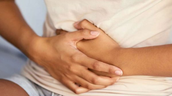 young woman holding tummy due to pain