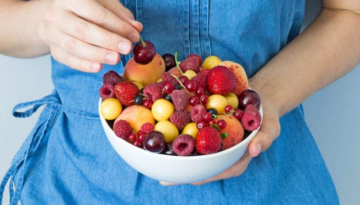 woman holding a bowl of fresh fruit salad