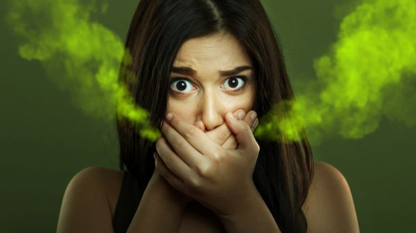 Woman with bad breath covering mouth