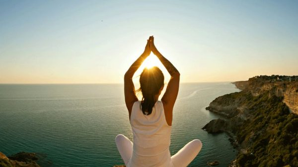girl doing yoga pose with sunset background