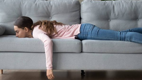Bored woman lying down on a sofa