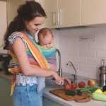 Mom preparing food while carrying baby